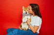 canvas print picture - Cute brunette woman in white t shirt and jeans holding and kissing Shiba Inu dog in silver decoration on plane red background. Love to the animals, pets concept