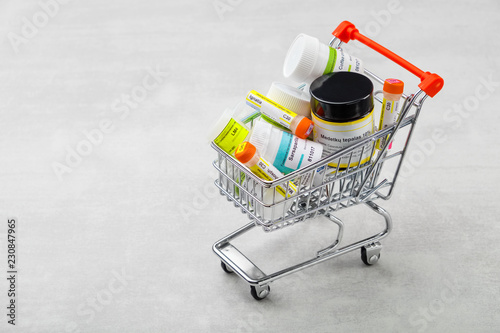 Photo  Mini shopping cart full of homeopathic remedies on blue background