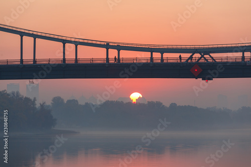 Sunrise view of pedestrian Park bridge and Dnipro river in Kyiv, Ukraine