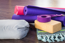 Variety Of Yoga Props On Wooden Floor In Studio. Pink And Purple Rolled Mats, Cork Brick, Belt, Grey Bolster And Folded Cotton Mat