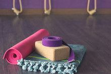 Pink Mat Rolled Up, Cork Block, Purple Belt And Colorful Cotton Mat In Yoga Center Wooden Floor. Various Yoga Props On Studio. Calisthenics Ropes On Background. Wellness Activity Concept