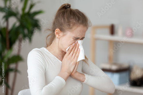 Photo Young millennial sick woman sitting alone at work office sneeze holding tissue handkerchief and blowing wiping her running nose