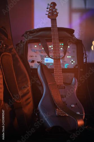 Spoed Foto op Canvas Muziekwinkel Electric guitar stands on the stage in a darkish room or studio.