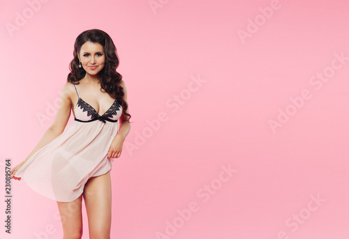 Fotografía  Front view of pretty seductive woman holding by hands and playfully raises short dress up
