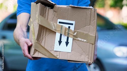 Fotografía  Frightened delivery worker giving broken customer parcel, shipment accident