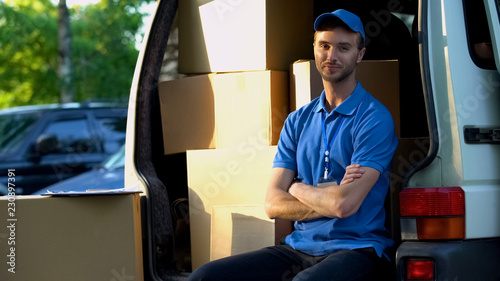 Fotografie, Obraz  Deliveryman smiling into camera, sitting in van, fast parcels transportation