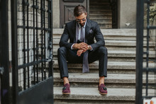 Businessman Waiting On The Stairs And Looking At The Time