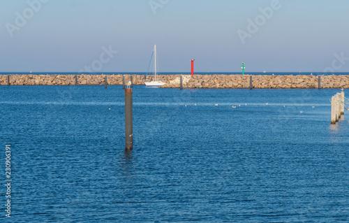 Tuinposter Poort Segelboot in einer Hafeneinfahrt