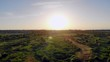 Aerial, rising drone shot, over bushes and green nature, towards the sunset , on a sunny evening, on Cenetennial beach, in British Columbia, Canada