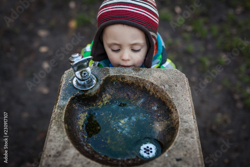 Fotografie, Obraz  thirsty boy at a drinking fountain