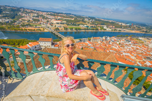 Foto op Canvas Barcelona Carefree tourist woman with open arms from top of bell Clock Tower. Caucasian female tourist enjoys in Central Portugal, Coimbra cityscape panorama and university courtyard on Mondego river.