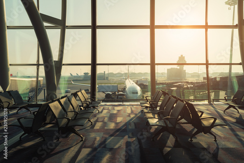 Foto auf Gartenposter Flughafen Empty chairs in the departure hall at airport with airplane taking off at sunset. Travel and transportation in airport concepts.