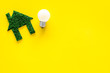 canvas print picture - Enegry saving technology concept. House cutout made of green grass near light bulb on yellow background top view copy space