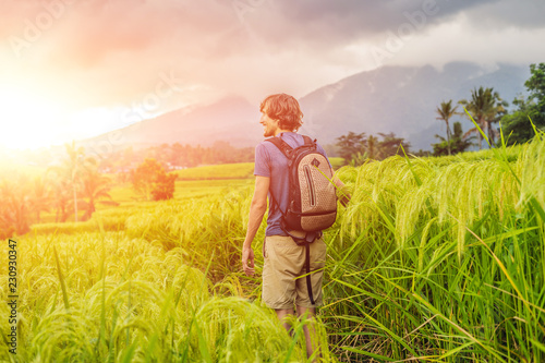 Young man traveler on Beautiful Jatiluwih Rice Terraces against the background of famous volcanoes in Bali, Indonesia with sunlight