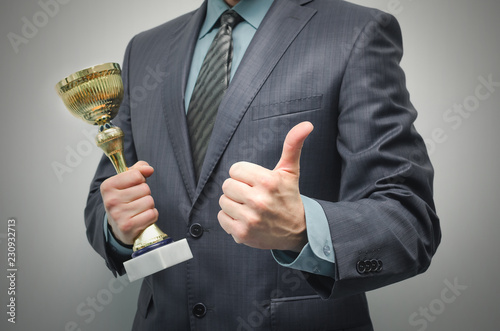 Photo Businessman is holding a golden award trophy in the hands and is showing a thumbs up isolated on gray background