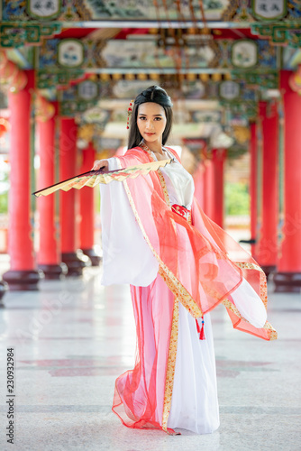 Beautiful Chinese woman with a traditional suit with blow in her hands, Beautiful and belligerent face, Young Samurai Canvas Print