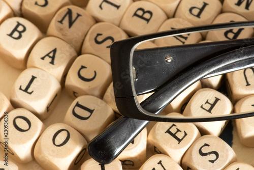 Fotografía  Eine Lesebrille und verschiedene Holzbuchstaben im Hintergrund