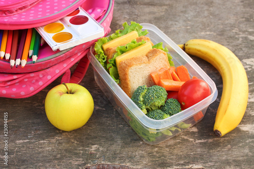 In de dag Assortiment Sandwiches, fruits and vegetables in food box, backpack on old wooden background.