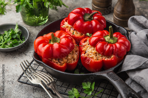 Obraz red bell peppers stuffed with meat, rice and vegetables on cast iron pan - fototapety do salonu