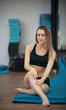 Young beautiful blonde girl in yoga class posing. Healthy lifestyle in fitness club. Stretching