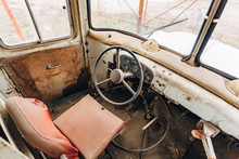Inside Old Time Abandoned Bus Driver Place. Rusty Cabin And Broken Dashboard