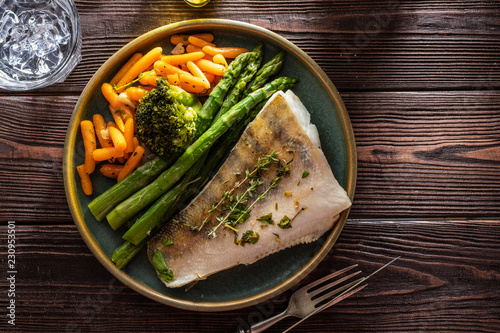 Pike perch fillet with asparagus, broccoli and carrots. Fried fish with stewed greens
