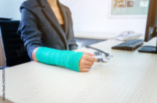Blurred Woman With Broken Hand And Green Cast Working On