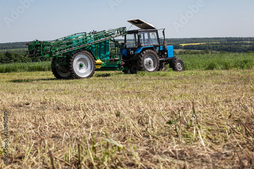 blue tractor in the field is preparing for chemical treatment of plants