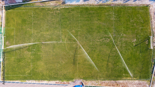 Aerial view of watering the lawn of a football field, top view