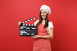canvas print picture - Housewife female chef cook or baker in striped apron, white t-shirt, toque chefs hat isolated on red wall background. Woman holding classic black film making clapperboard. Mock up copy space concept.