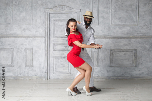 A white girl in a red dress and a black man in a white suit are dancing an incendiary dance.