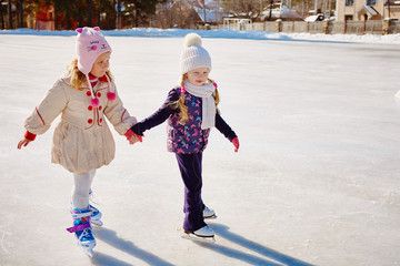 Two little girls hold hands and skate.