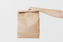 Close Up Female Holds In Hand Brown Clear Empty Blank Craft Paper Bag For Takeaway Isolated On White Background. Packaging Template Mockup. Delivery Service Concept. Copy Space. Advertising Area.