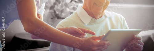 Female nurse showing medical report to senior man on digital Obraz na płótnie
