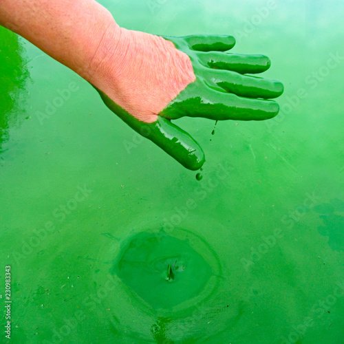 Human hand polluted by green harmful substance and liquid splash Canvas Print