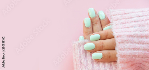 Photo sur Toile Manicure Tender hands with perfect blue manicure on trendy pastel pink background. Place for tex