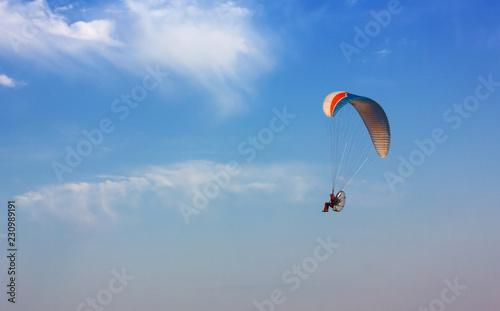 Flying Paramotor against a Blue Sky