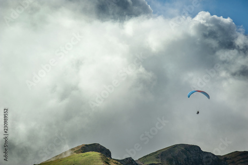Poster Luchtsport Paraglider flies over the mountains