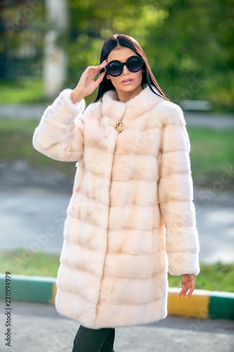 Fotografie, Tablou  Beautiful brunette in sunglasses and a light fur coat walking down the street