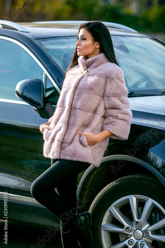 Fotografie, Obraz  A beautiful brunette in a light fur coat and black trousers is standing near the
