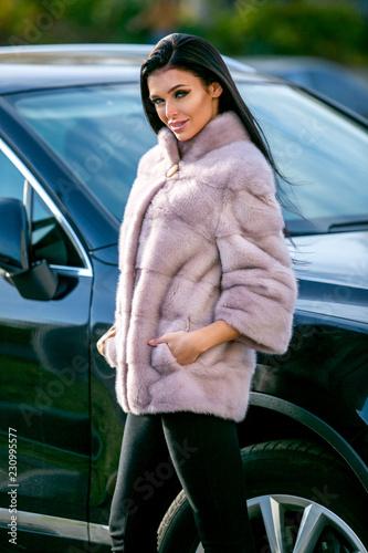 Fotografia, Obraz  A beautiful brunette in a light-colored fur coat and black trousers is standing
