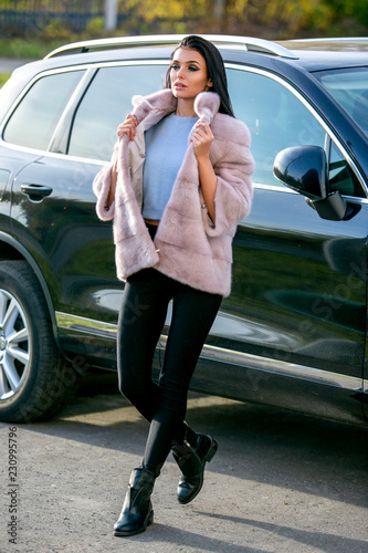 Fotografie, Tablou  A beautiful brunette in a light fur coat and black trousers walks down the stree