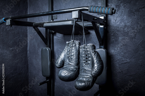 Old boxing gloves on a dark background.