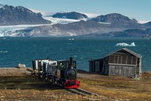 Historic Mine Train In Front Of The Kongsfjorden, Ny-Alesund, Spitsbergen, Svalbard Islands, Svalbard And Jan Mayen, Norway, Europe