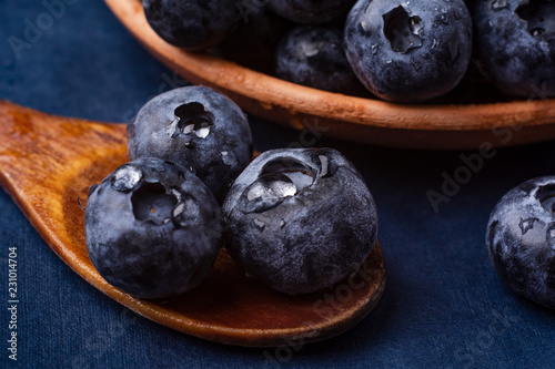 bog whortleberry in a wooden spoon on a blue background Fototapet