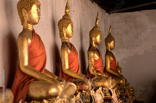 Fotografia  Close up shiny golden buddha statues in a row with beam of light in buddhist tem