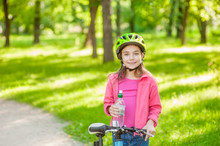 Smiling Little Girl With Water By The Bike. Space For Text