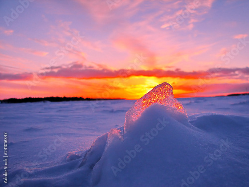 Papiers peints Rose clair / pale Transparent piece of ice on the snow against the backdrop of a winter sunset