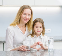 Little Girl With A Glass Of Water And Happy Mother At Kitchen