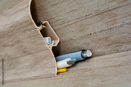Fotografie, Obraz  stripped wires protrude from the floor skirting